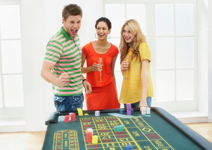 Young man with friends celebrating gambling win at roulettの写真素材 [FYI03637160]