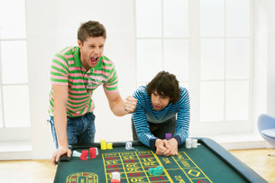 Young man celebrating gambling win at roulette tableの写真素材 [FYI03637161]