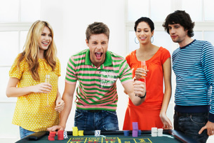 Young man with friends celebrating gambling win at roulettの写真素材 [FYI03637163]