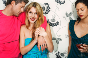 Young woman with friends by floral print wall  portraitの写真素材 [FYI03637164]