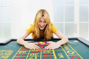 Happy woman at roulette table collecting chipsの写真素材 [FYI03637165]