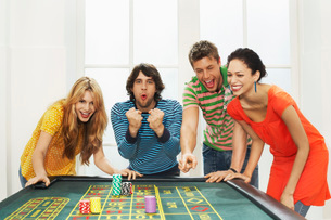 Friends celebrating win on roulette tableの写真素材 [FYI03637176]
