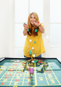 Young woman celebrating with chips on roulette tableの写真素材 [FYI03637179]