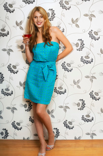 Woman standing by floral print wall Drinking Martini  portの写真素材 [FYI03637209]