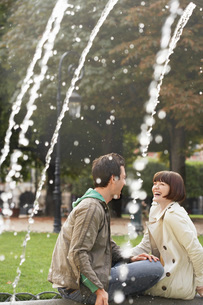 Couple laughing sitting on edge of fountain  view past watの写真素材 [FYI03637245]
