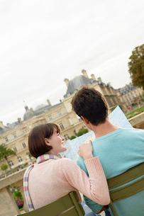 Young couple sitting on chairs  looking at map  in park  bの写真素材 [FYI03637250]