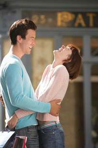 Laughing couple embracing in front of shopの写真素材 [FYI03637253]