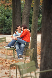 Couple eating snack  sitting on chairs  in parkの写真素材 [FYI03637255]