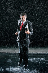 Businessman holding binder  running in Rainの写真素材 [FYI03637262]