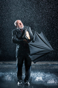 Businessman struggling to open umbrella during Sudden Rainの写真素材 [FYI03637265]