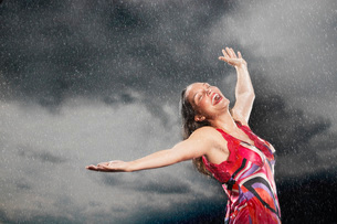 Woman  arms outstretched  smiling  standing in rainの写真素材 [FYI03637270]