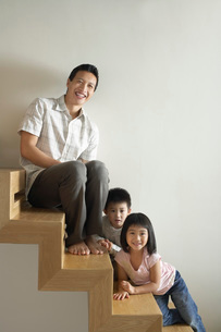 Father Sitting with Children on wooden Staircaseの写真素材 [FYI03637309]