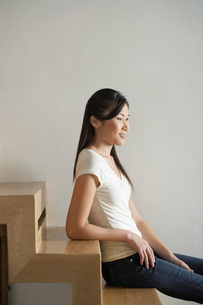 Young Woman Sitting on wooden staircase  side viewの写真素材 [FYI03637310]