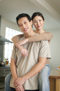 Wife sitting on countertop  arms around standing husbandの写真素材 [FYI03637318]