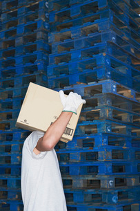 Warehouse Worker Carrying Box past stack of pallets  sideの写真素材 [FYI03637349]