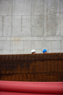 Two men at construction site behind stack of rebarの写真素材 [FYI03637372]
