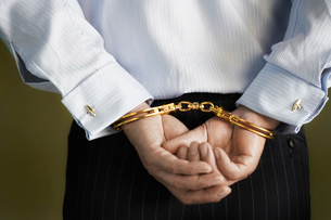 Businessman standing with hands handcuffed behind back  miの写真素材 [FYI03637386]