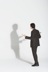 Young businessman standing  arguing with own shadowの写真素材 [FYI03637398]