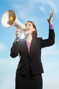 Smiling  Mid-adult woman shouting through megaphone outsidの写真素材 [FYI03637405]