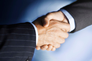 Middle-aged businessmen shaking hands  close-up  digitallyの写真素材 [FYI03637411]