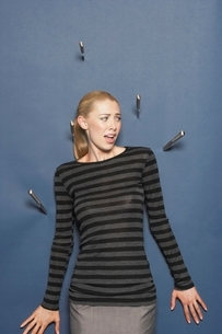 Woman surrounded by thrown knives against blue backgroundの写真素材 [FYI03637419]