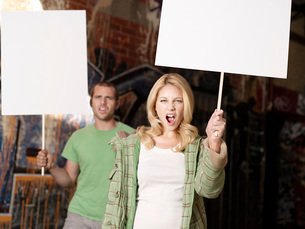Young man and woman holding blank demonstration placardsの写真素材 [FYI03637434]
