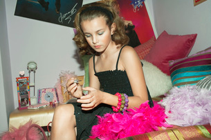 Fashionable Young Girl Applying Nail Polish in trendy bedrの写真素材 [FYI03637490]
