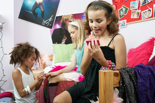 Fashionable Young Girls Applying Makeup in trendy bedroomの写真素材 [FYI03637492]