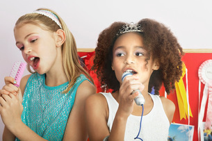 Girls using brushes  microphones to sing at a Slumber Partの写真素材 [FYI03637497]