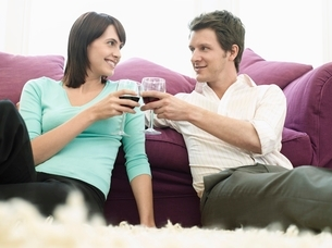 Young couple relaxing on sofa  toasting with wineの写真素材 [FYI03637531]