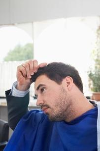 Business man holding freshly cut hair in barbersの写真素材 [FYI03637565]