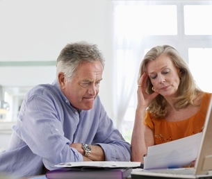 Senior couple looking at bills  sitting at dining tableの写真素材 [FYI03637566]