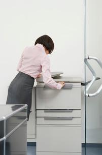 Woman using photocopier in officeの写真素材 [FYI03637575]