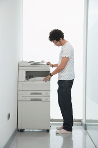 Man using copy machine in hallwayの写真素材 [FYI03637584]