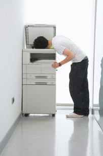 Man putting his head in copy machine in hallwayの写真素材 [FYI03637587]