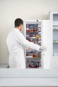 Scientist looking in refrigerator of specimens in laboratoの写真素材 [FYI03637595]