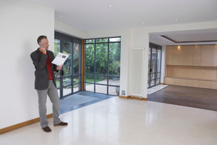 Real estate agent using mobile phone in new propertyの写真素材 [FYI03637612]