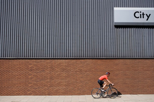 Man cycling past building with 'City' written on sideの写真素材 [FYI03637618]