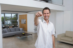 Man holding key in new home  portraitの写真素材 [FYI03637622]