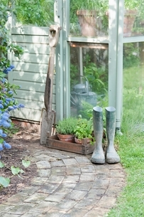 Garden tools and wellington boots outside greenhouseの写真素材 [FYI03637671]