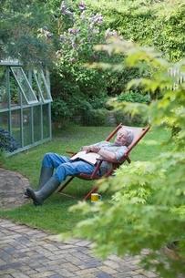 Gardener sleeps on deckchair in back gardenの写真素材 [FYI03637672]