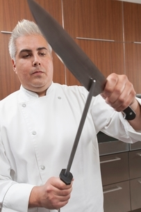 Mid- adult chef sharpens knifeの写真素材 [FYI03637755]