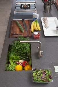 Fresh food preparation on kitchen counter with sinkの写真素材 [FYI03637759]