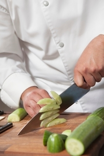Mid- adult chef slicing cucumberの写真素材 [FYI03637766]