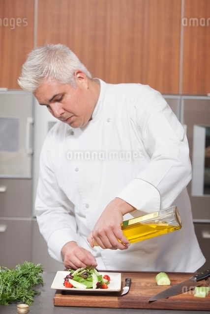 Mid- adult chef pours olive oil over side saladの写真素材 [FYI03637770]