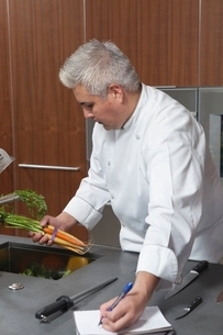 Mid- adult chef holding carrots and writing in notebookの写真素材 [FYI03637775]