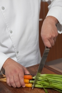 Mid- adult chef cutting carrotsの写真素材 [FYI03637780]