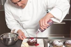 Mid- adult chef puts finishing touches on chocolate cakeの写真素材 [FYI03637789]