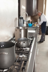 Chef works in kitchen with saucepans on hobの写真素材 [FYI03637799]