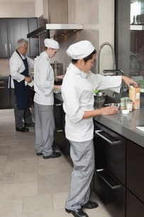 Three chefs work together in busy kitchenの写真素材 [FYI03637806]